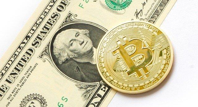 Moneda de oro BTC en la parte superior de un dólar