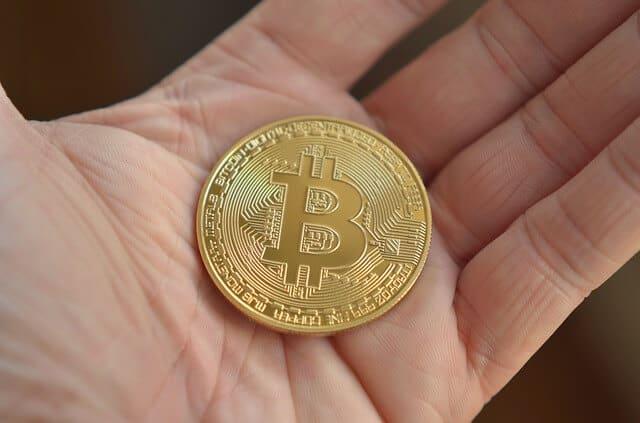 Moneta d'oro BTC in mano
