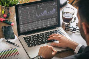 Dizüstü bilgisayarında Anında Kar ticaret platformunu kullanan adam, ekranda uygulama izleme, ofis masası arka planı.